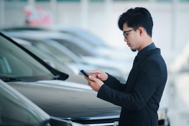 Empresário bonito de terno e óculos falando ao telefone no escritório felicitar as vendas foram concluídas para o novo showroom de carro. Foto Premium