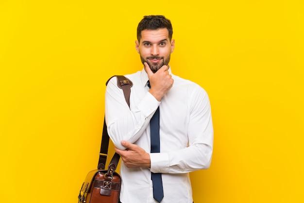 Empresário bonito sobre parede amarela isolada rindo Foto Premium