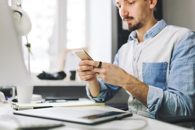Empresário bonito trabalhando no escritório usando telefone celular Foto gratuita