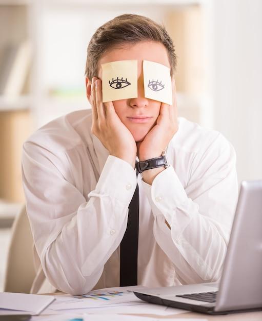 Empresário cansado com nota adesiva em seus olhos. Foto Premium