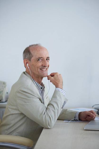 Empresário caucasiano sênior com fones de ouvido sentado no escritório Foto gratuita