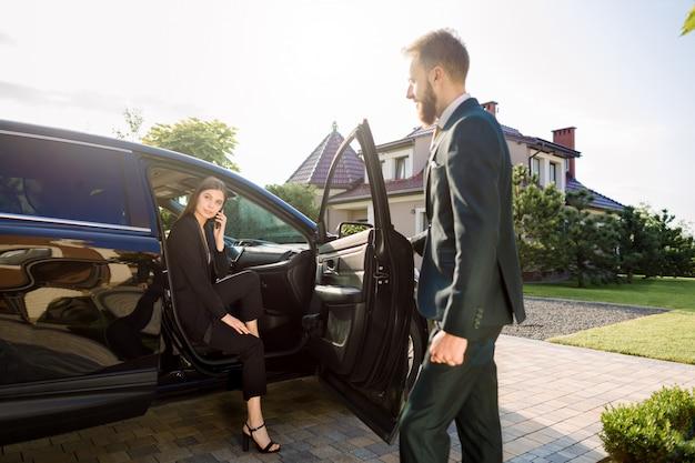 Empresário chegando ao carro e abre a porta para jovem, falando ao telefone. a mulher de negócios sai do automóvel e está pronta para ir com seu colega ao prédio de escritórios Foto Premium