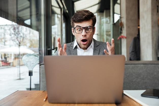 Empresário chocado em óculos, sentado junto à mesa no café, olhando para o computador portátil Foto gratuita