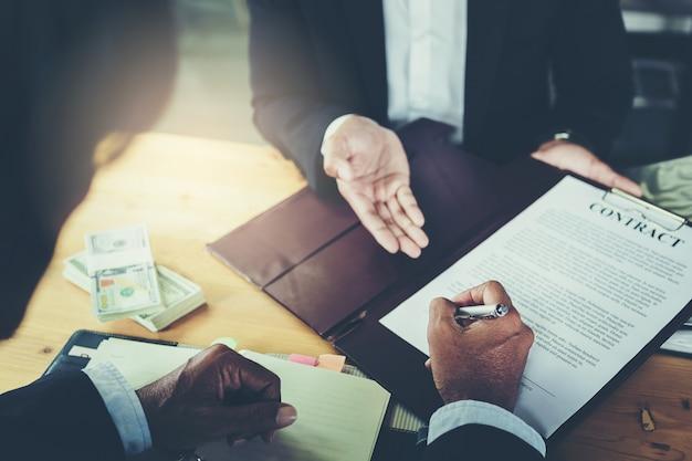 Empresário coloca assinatura no contrato na reunião de negócios e passar dinheiro após negociações Foto Premium