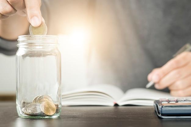 Empresário, colocando a moeda no copo jar e gravar no notebook. está economizando e investindo Foto Premium