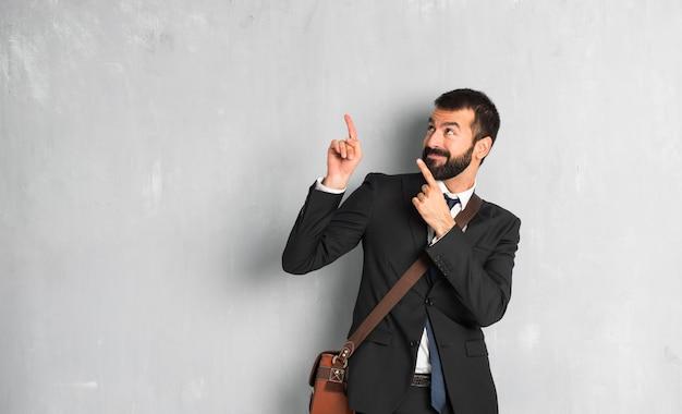 Empresário com barba apontando com o dedo indicador e olhando para cima Foto Premium