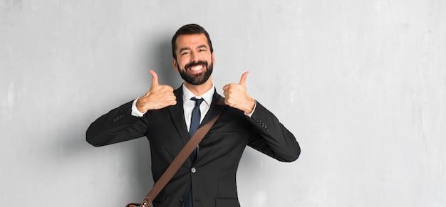 Empresário com barba dando um polegar para cima gesto porque teve sucesso Foto Premium