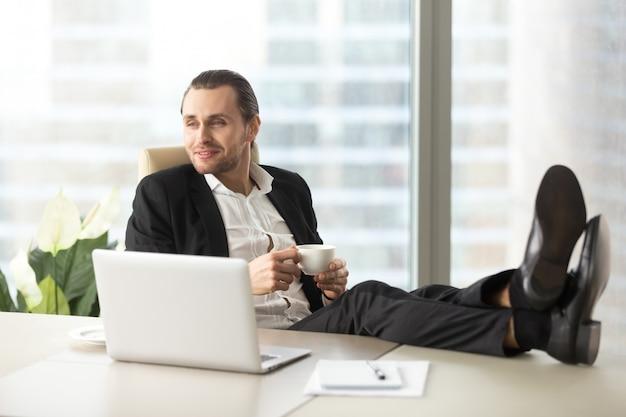 Empresário com café imagina feliz futuro Foto gratuita