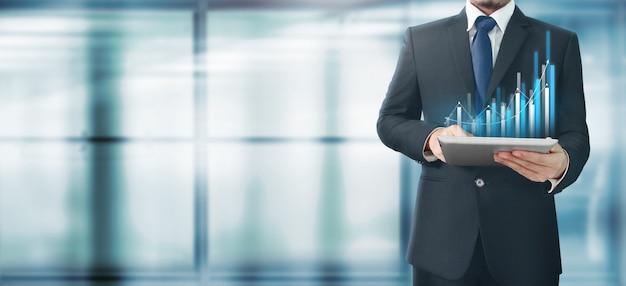 Empresário com gráfico em seu tablet de negócios na mão Foto Premium