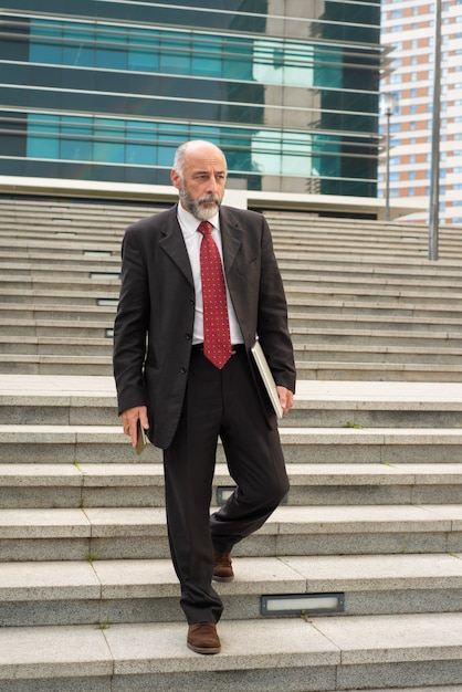 Empresário com laptop e smartphone andando nos degraus Foto gratuita