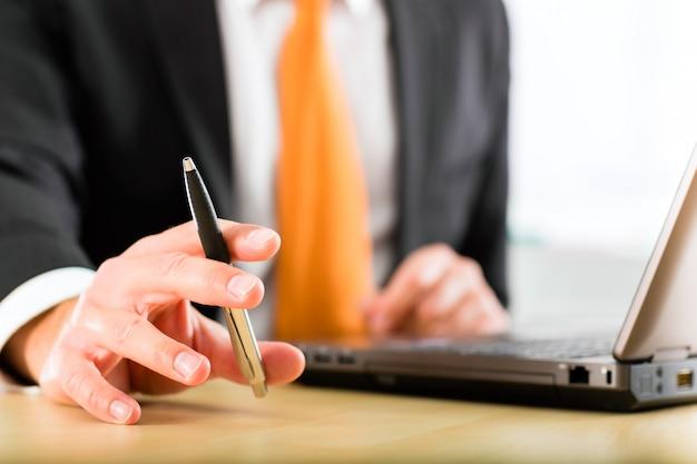 Empresário com laptop em seu escritório de negócios Foto Premium