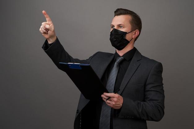 Empresário com máscara médica cirúrgica, apontando com o dedo ...