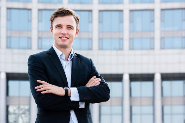 Empresário com os braços cruzados, olhando para a câmera Foto gratuita
