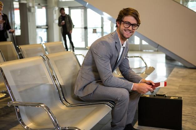 Empresário com passaporte, cartão de embarque e maleta sentado na sala de espera Foto gratuita