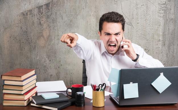 Empresário com raiva, falando com o telefone na mesa do escritório. Foto gratuita