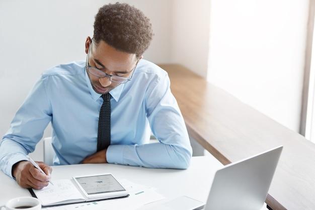 Empresário confiante trabalhando em seu laptop Foto gratuita