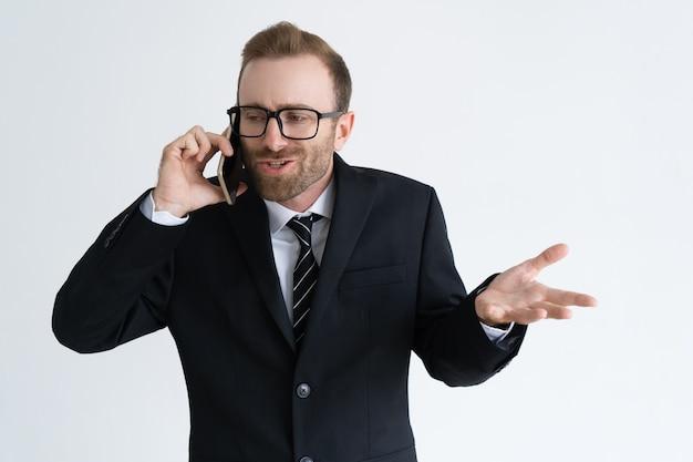 Empresário confuso em jaqueta preta falando no telefone Foto gratuita