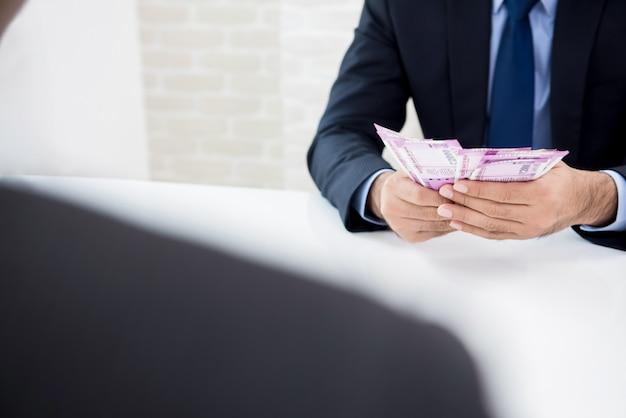 Empresário contando dinheiro, moeda da rúpia indiana, recém-recebida de seu parceiro Foto Premium