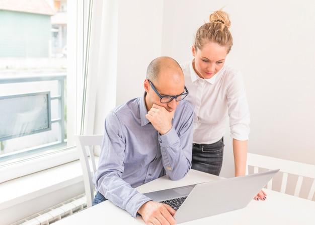 Empresário contemplativo e empresária olhando para laptop Foto gratuita