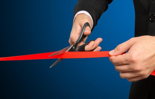 Empresário, corte a fita vermelha com um par de tesouras Foto Premium