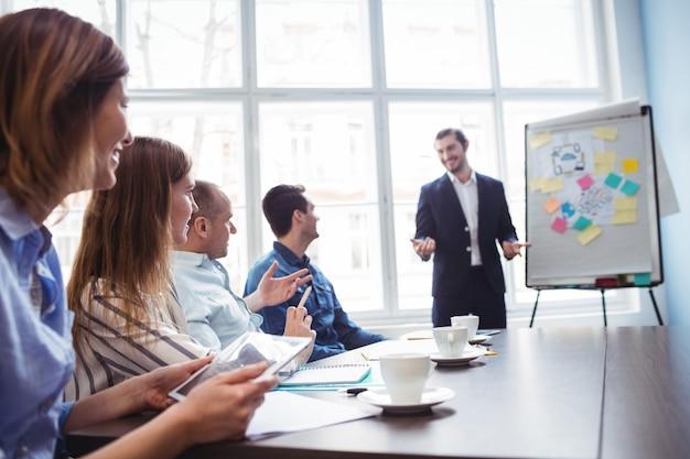 Empresário dando apresentação na frente de colegas de trabalho Foto Premium