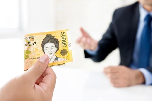 Empresário dando dinheiro ao seu parceiro em forma de won sul-coreano Foto Premium