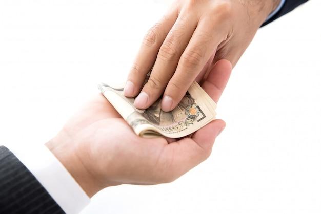 Empresário dando dinheiro, notas de ienes japoneses, ao seu parceiro Foto Premium