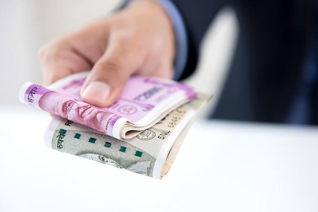 Empresário dando dinheiro sob a forma de rúpias indianas f Foto Premium