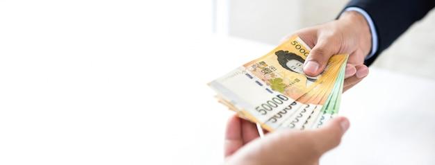 Empresário dando dinheiro won sul-coreano moeda para seu fundo de banner de parceiro Foto Premium