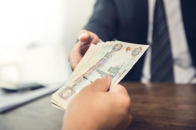 Empresário dando notas de dinheiro dirham dos emirados árabes unidos para seu parceiro Foto Premium