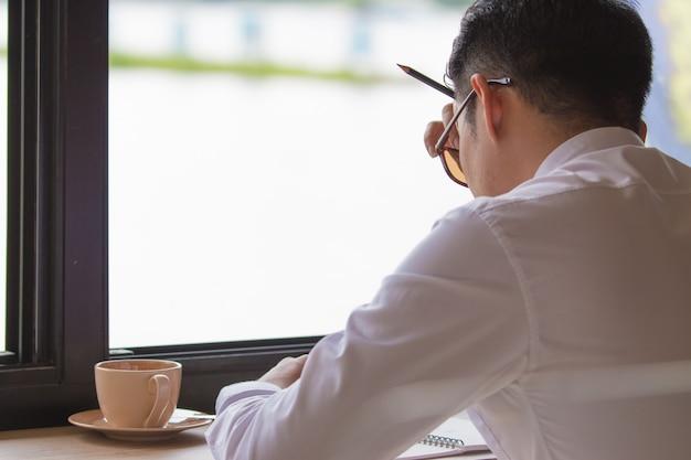 Empresário de ásia não fesh, sonolento e bocejando, fundo de loja de café Foto Premium