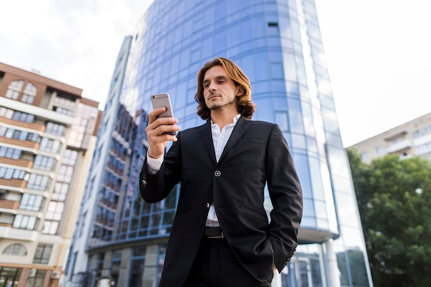 Empresário de baixo ângulo atirou usando um telefone Foto gratuita
