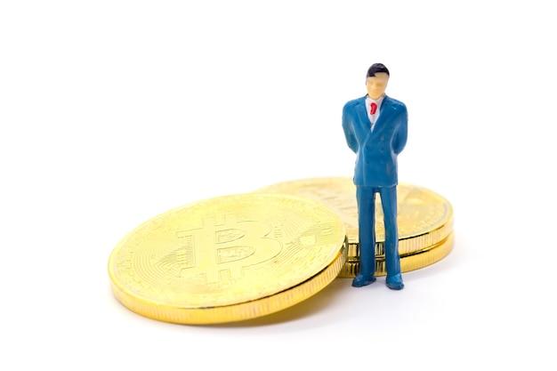 Empresário de brinquedo e bitcoin em fundo branco Foto Premium