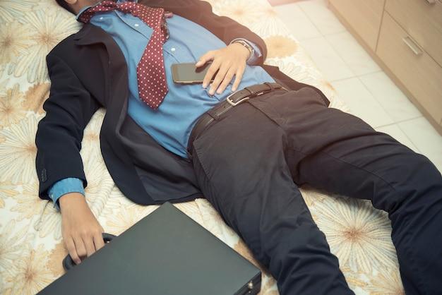 Empresário de cansaço dormindo no terno com bolsa e celular Foto Premium