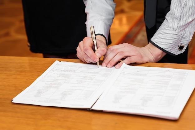 Empresário de homem assina documentos com uma caneta Foto Premium