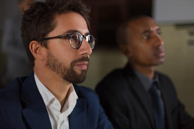Empresário de óculos, trabalhando no escritório escuro Foto gratuita