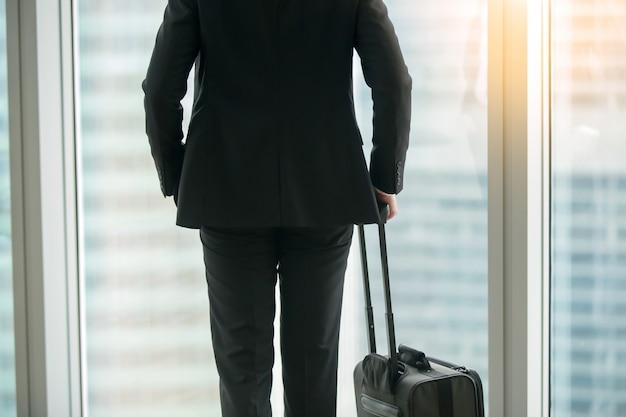 Empresário de pé com mala perto da janela Foto gratuita