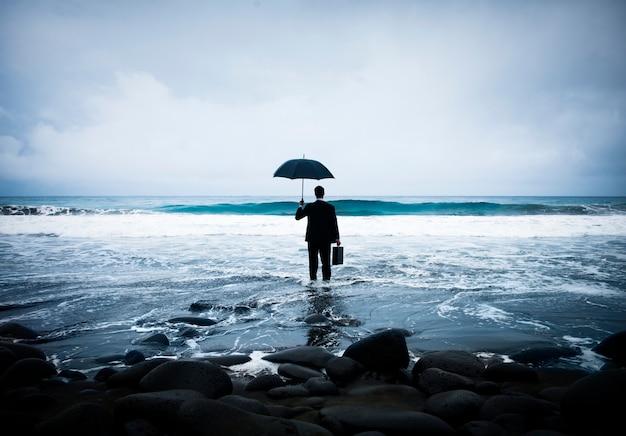Empresário de pé com um guarda-chuva no oceano Foto Premium
