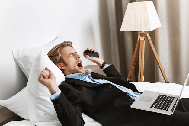 Empresário de retrato f barbudo deitado no quarto de hotel, segurando o telefone e o computador portátil, bocejando e indo dormir após um trabalho produtivo. Foto gratuita