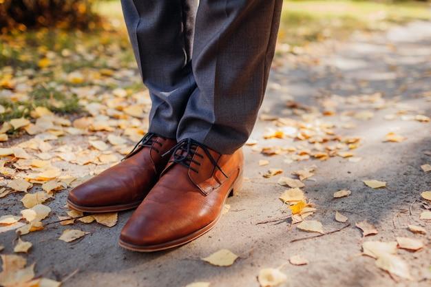 Empresário de sapatos no parque outono. calçado clássico em pele castanha. feche acima das pernas Foto Premium