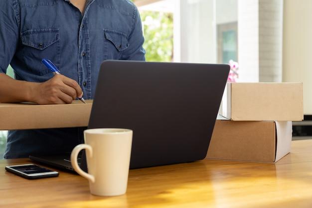 Empresário de sme mão escrevendo endereço na caixa de encomendas com café e telefone celular na mesa Foto Premium