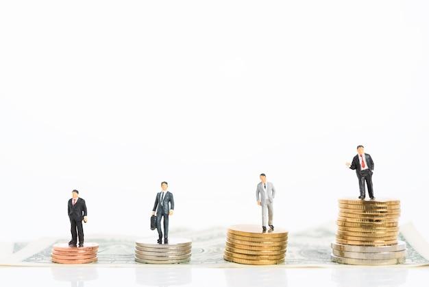 Empresário de sucesso miniture em terno preto trabalho em equipe fica em pé sobre moedas de ouro e prata isoladas no branco Foto Premium