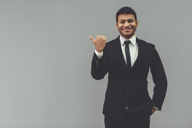 Empresário de terno clássico está apontando para longe. Foto Premium