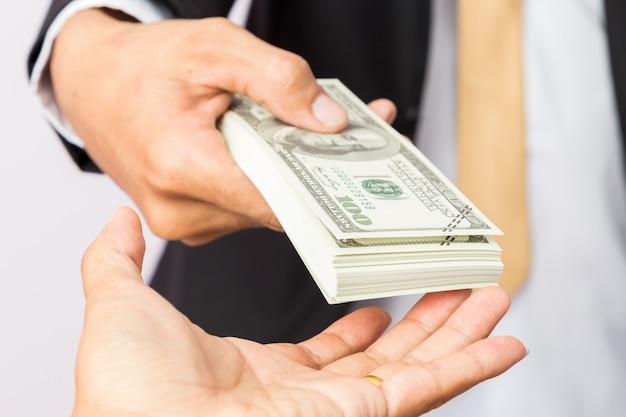 Empresário de terno dá dólares americanos a um homem Foto Premium
