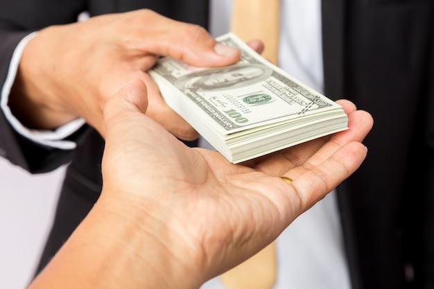 Empresário de terno dá dollors eua para um homem Foto Premium