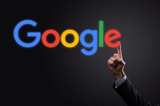 Empresário de terno em um fundo escuro mantém uma inscrição do logotipo do google. o google é o mecanismo de busca mais popular do mundo. Foto Premium