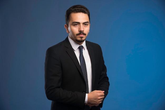 Empresário de terno preto com uma gravata posando. Foto gratuita