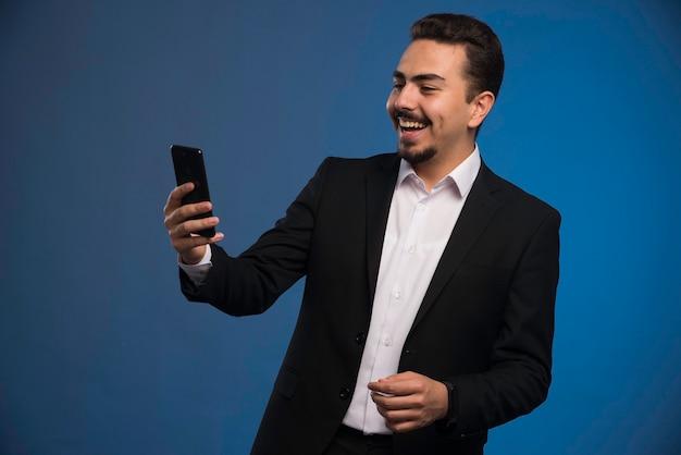 Empresário de terno preto, verificando o telefone. Foto gratuita