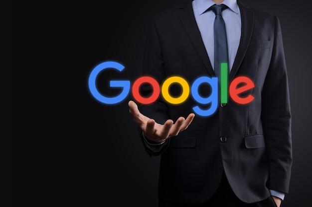 Empresário de terno segura um logotipo do google Foto Premium
