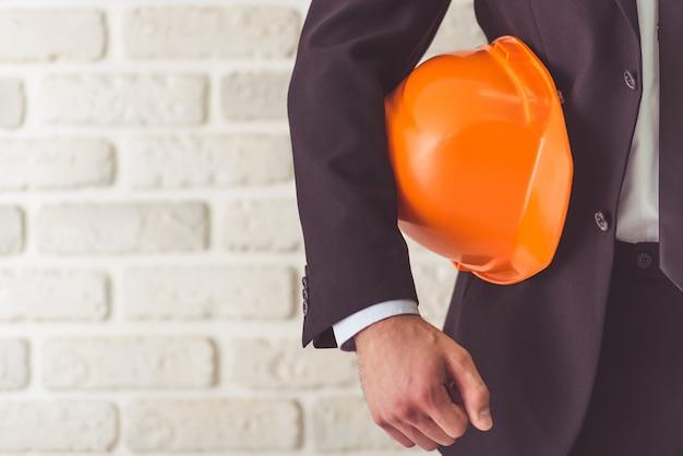 Empresário de terno segurando um capacete Foto Premium